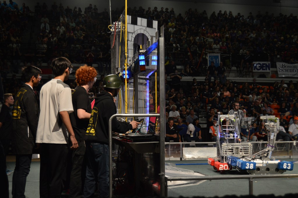 Aaron Fang, freshman, Michael Liu, senior, Jason Fowler, junior, and Brandon Bahn, junior, look on from the drivers' station as they maneuver their robot (blue, 3863) in defense against an opponent.